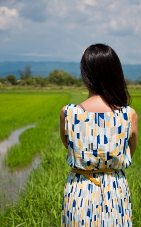The backside of asian woman near rice field in Thailand photo