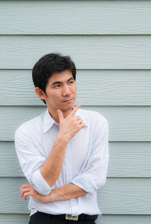An asian man cross his arm as thinink with wooden background Stock Photo