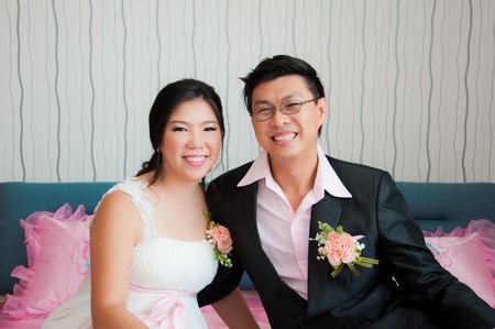 Les mari�s se asseoir sur le lit rose souriant � la cam�ra apr�s la c�r�monie de mariage Banque d'images