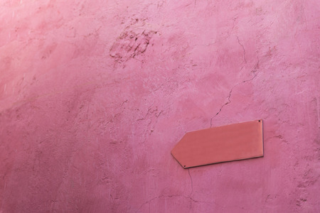 feature wall: The blank pink arrow sign made from feature board on the pink cement wall Stock Photo