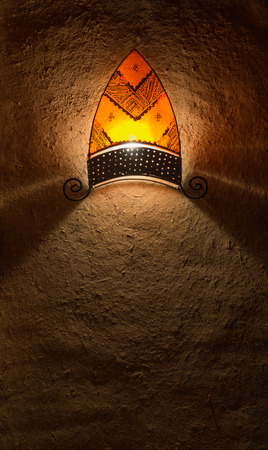 The traditional latern in arabian style hang on the soil wall photo