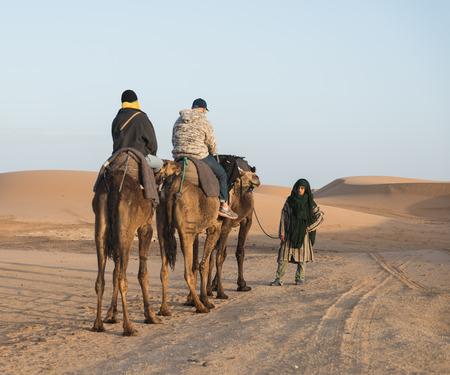 Merzouga Maroc le 17 mars: Le guide arabe prend une couple de touristes de monter chameau dans le d�sert du Sahara comme Desert tourn�e le 17 Mars 2014 au Merzouga ville Maroc.