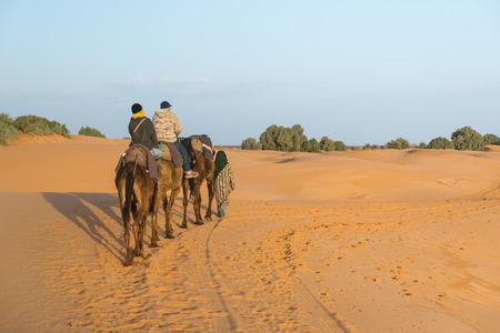 Merzouga, Maroc - Mar 18: Le guide arabe prend une couple de touristes de monter chameau dans le d�sert du Sahara comme Desert tourn�e le 18 Mars, 2014, la ville de Merzouga, au Maroc.
