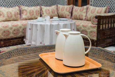 jugs: Two white jugs on the wooden table in Moroccan house prepared for breakfast in Fes, Morocco