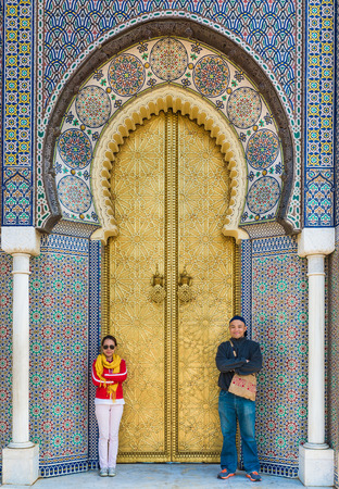 bab: Two asian tourist stand in front of Bab Dar Lmakhzen or the Royal Palace Gate in Fes, Morocco