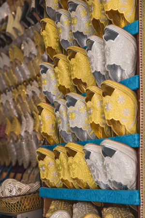 gold souk: The gold and silver traditional shoes of Morocco made from cloth for bride sell in the Medina in Fes, Morocco