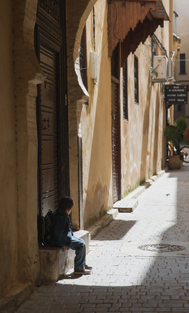 fes: Fes, Morocco - Mar 19: One boy sit in front of the door waiting for his parent after back from school in Medina on March 19, 2014 in Fes, Morocco