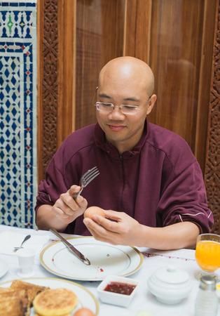 fork glasses: One bald man with glasses hold fork to hit boiled egg for breakfast