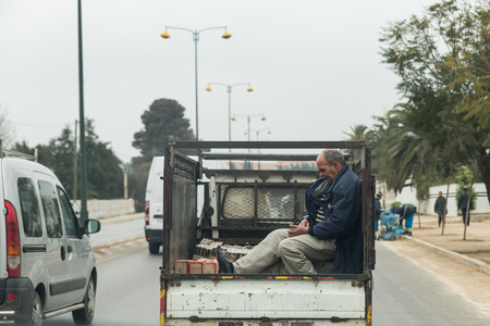 wares: Meknes, Morocco - Mar 20: One man wares overcoat sits in the truck and plays mobile phone during winter time on the way to Meknes on March 20, 2014 in Meknes, Morocco