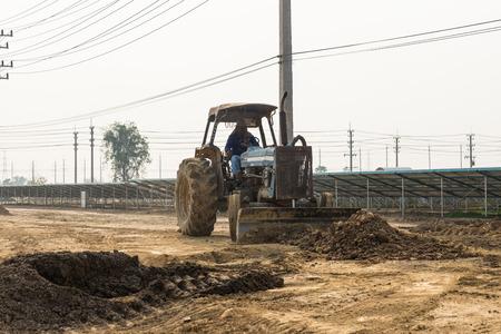 dozer: Petchaburi, Thailand - February 20, 2016: One worker drives wheel dozer in the under construction solar farm on February 20, 2016 in Petchaburi, Thailand Editorial