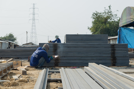 welds: Petchaburi, Thailand - February 20, 2016: The welder without personal safety protection welds  iron frame for making fence at prepared area for construction on February 20, 2016 in Petchaburi, Thailand
