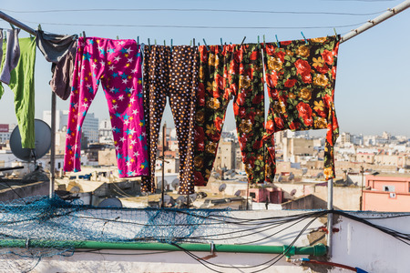 bask: The colourful long plants bask on the clothes line on the roof top of building in Casablanca, Morocco Stock Photo