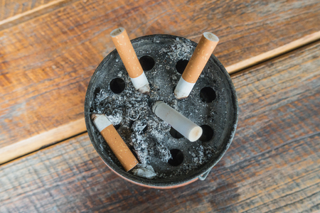 The ash of cigarettes on the ashtray with wooden background