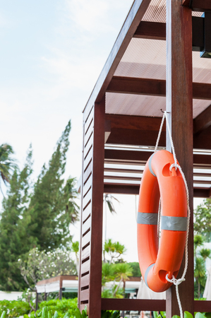 The orange life buoy hangs at the wooden station near beach in Thailand