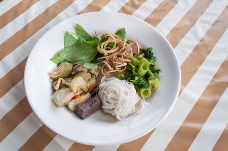 The thai rice vermicelli with chicken green curry beside with sweet basil, morning glory lesser ginger and small eggplant Stock Photo