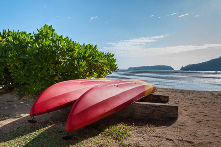 Two red-yellow kayak turn on the beach near sea with blue sky in Phuket, Thailand