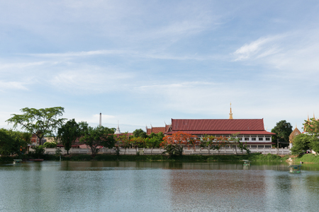 The thai temple near lake with blue sky in Chainart, Thailand