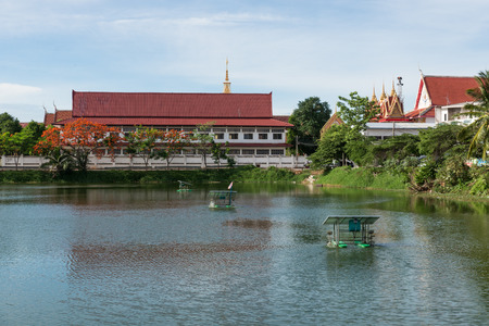 The thai temple near lake with water turbine by solar cell in Chainart, Thailand Stock Photo