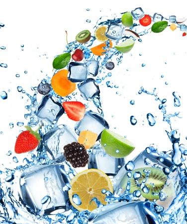 cubos de hielo: Fruta fresca en salpicaduras de agua con cubitos de hielo Foto de archivo