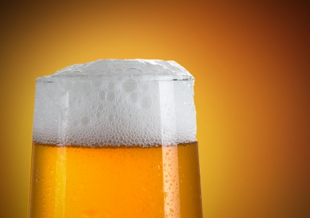 Beer in a glass with gold background Stock Photo - 14516969