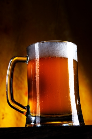 Beer in a glass with gold background  photo