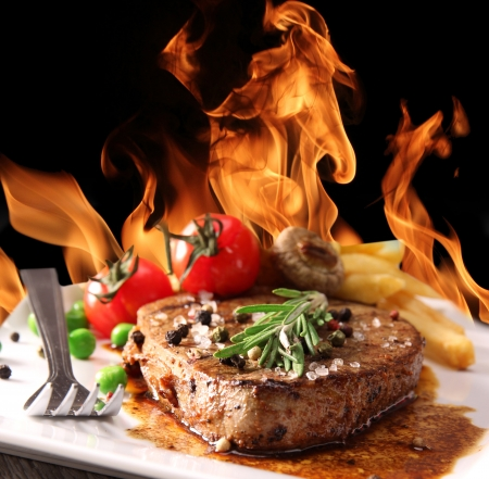 Grilled Beef Steak with fire flames photo