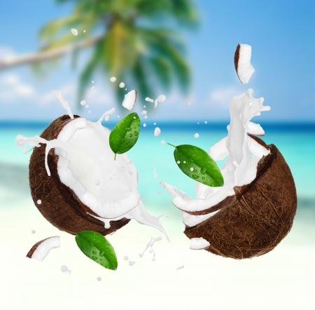 Coconut with milk splash on the beach Standard-Bild