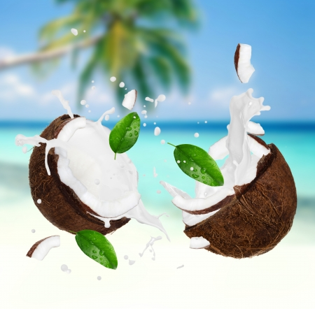 Coconut with milk splash on the beach Banque d'images