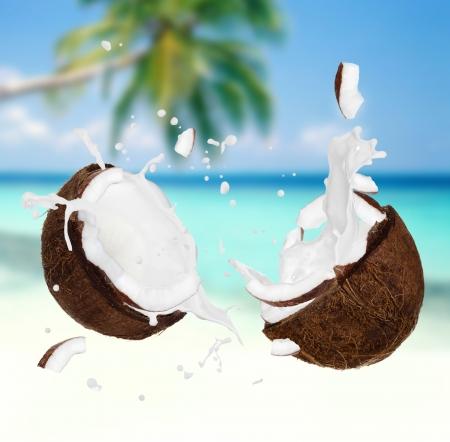 Coconut with milk splash on the beach  Stock Photo