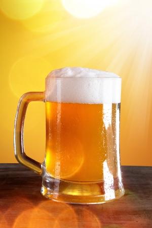 Bicchiere di birra con fondo oro Archivio Fotografico
