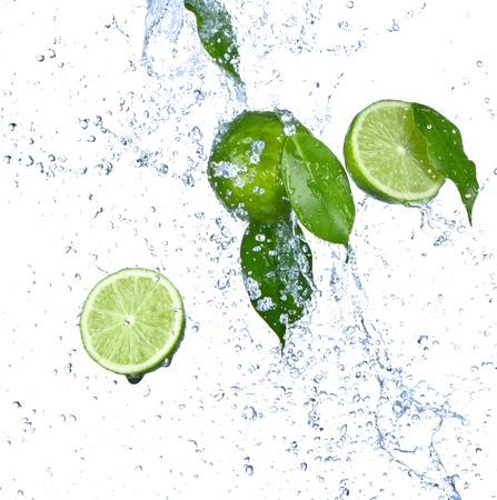 lima limon: Limas frescas con salpicaduras de agua aislados en blanco