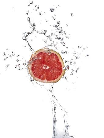 toronja: Pomelo fresco con el chapoteo del agua aislado en blanco Foto de archivo