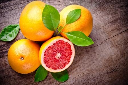 grapefruit: Freshly harvested grapefruits on wooden background