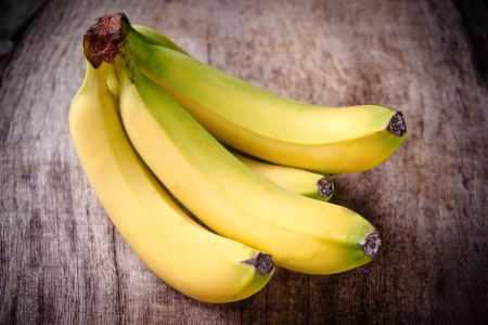 Freshly harvested bananas on wooden background photo