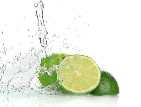 glass block: Green limes with splashing water  Stock Photo