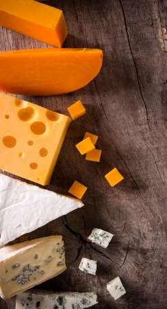 sliced cheese: Various types of cheese on wooden background