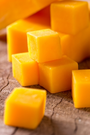 cheddar: Cheese cubes on wooden background