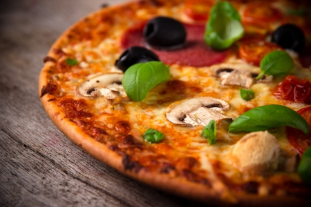 Tasty Italian pizza on wooden background Banco de Imagens