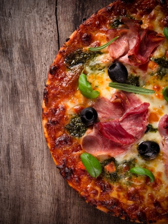 Tasty Italian pizza on wooden background photo