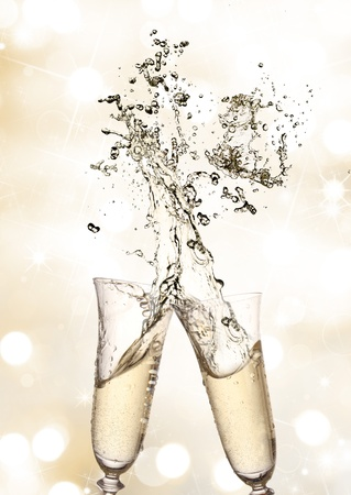 champagne bubbles: Pair of champagne flutes making a Champagne splash  Stock Photo