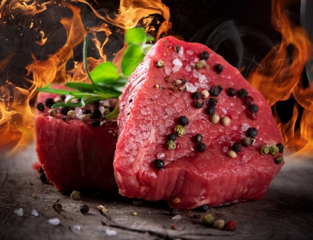 Raw beef steaks with fire flames Stock Photo - 15764382