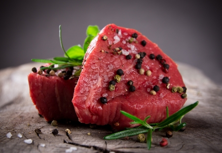 carne cruda: Filetes de carne fresca en la mesa de madera