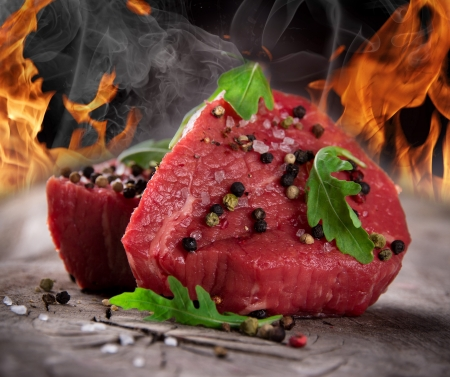 Raw beef steaks with fire flames Stock Photo - 15764378