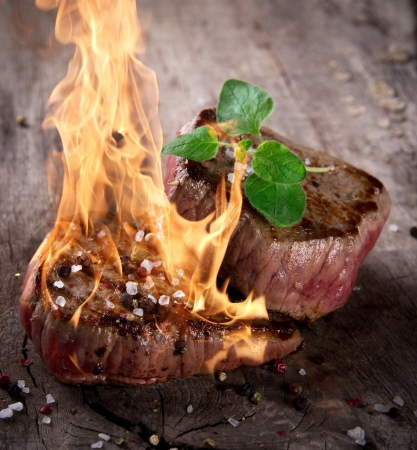 Grilled bbq steaks with fire flames photo