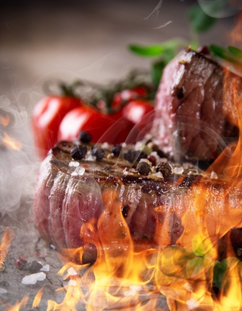 Grilled bbq steaks with fire flames Stock Photo - 15764373