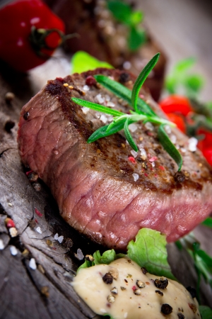 Medium grilled bbq steak with fresh herbs and tomatoes Stock Photo - 15764400