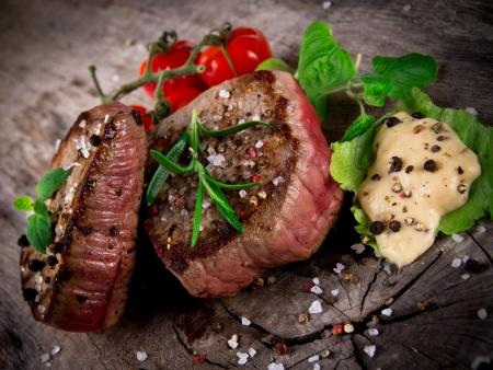 bistecche: Medio bistecche alla griglia barbecue con erbe fresche e pomodori Archivio Fotografico