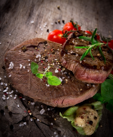 Grilled 500g bbq steak on wooden table photo