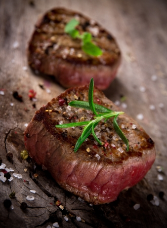 Grilled bbq steaks on wooden background photo