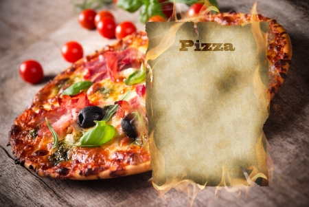 cold cuts: Tasty Italian pizza with burning blank paper Stock Photo